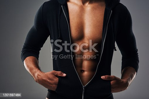 Cropped shot of an unrecognizable muscular young man posing in a zipped down hoodie against a grey background