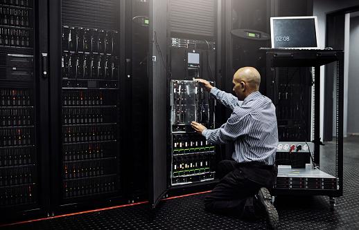 Rearview shot of an IT technician repairing a computer in a data center