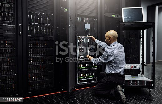 Rearview shot of an IT technician repairing a computer in a data center