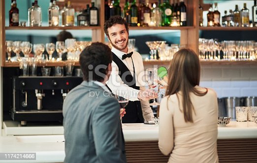 Cropped shot of a handsome young barman serving a young couple in a bar