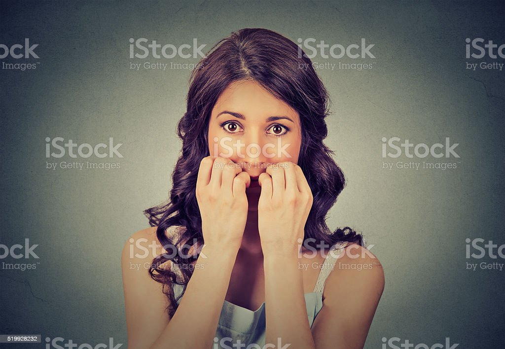 hesitant nervous woman biting her fingernails craving something stock photo