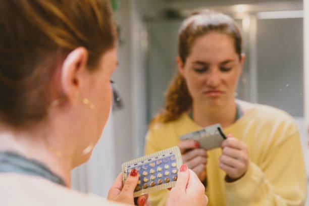 피임 알 약을 보고 주저 여자 - 가족 계획 뉴스 사진 이미지