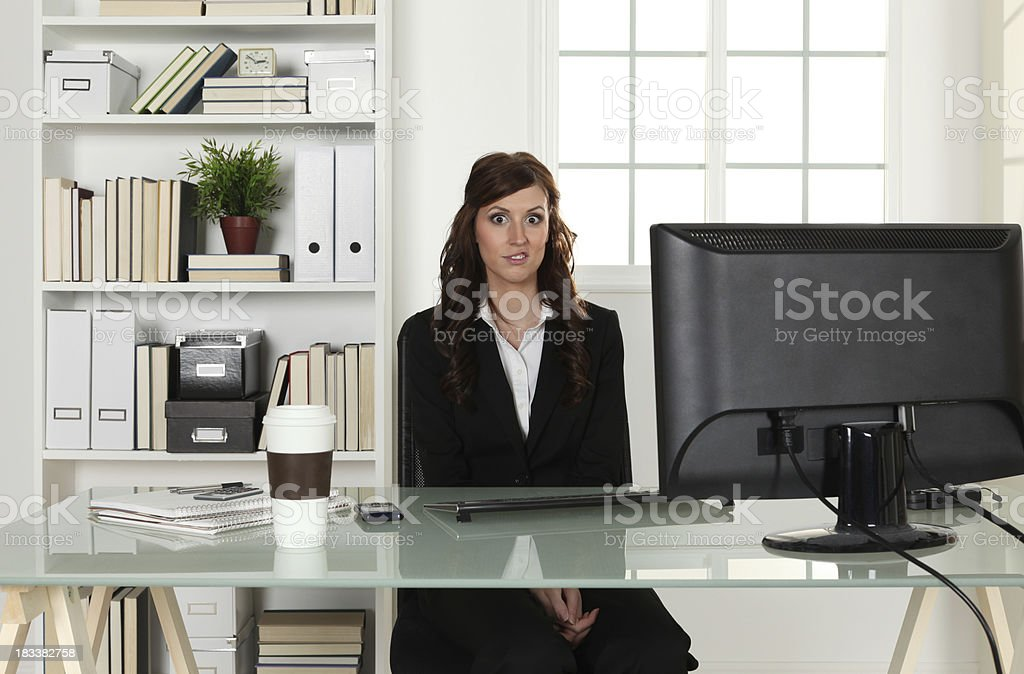 Hesitant young businesswoman in her office royalty-free stock photo