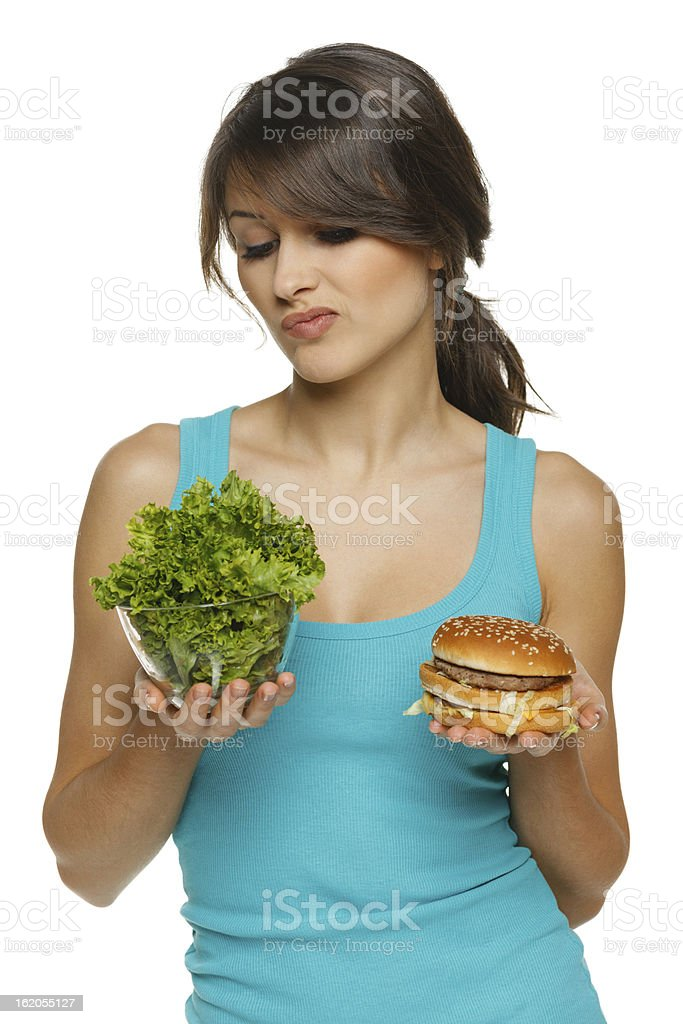 Hesitating woman making decision between healthy salad and fast food royalty-free stock photo