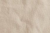 Hessian sackcloth woven fabric texture background in beige cream brown color