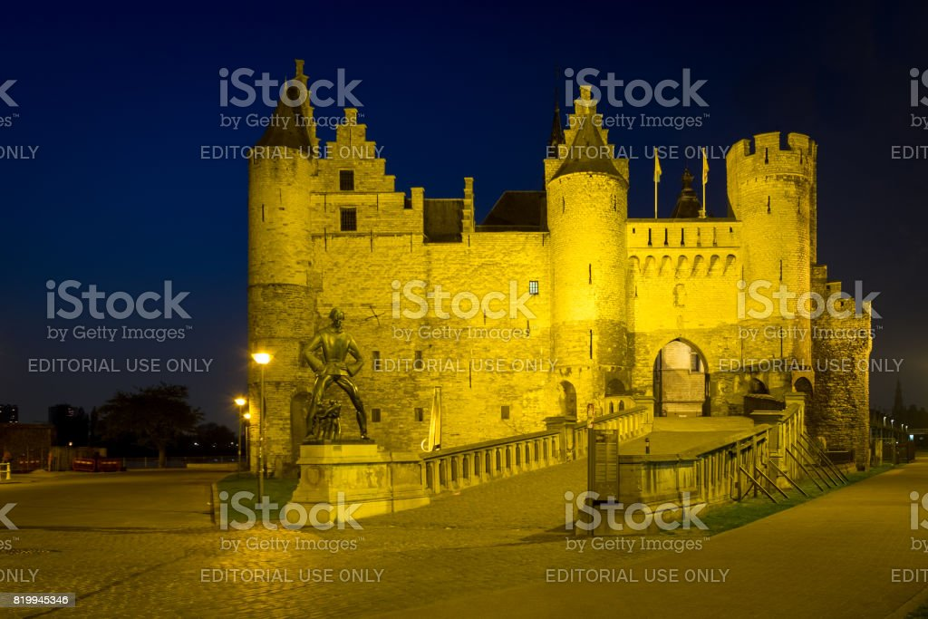 'Het Steen' fortress with the Lange Wapper monument during blue hour in Antwerp stock photo