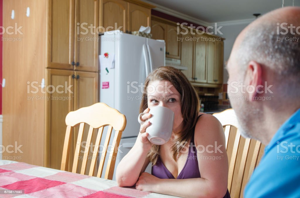 Heterosexual couple discussing at table with coffee stock photo