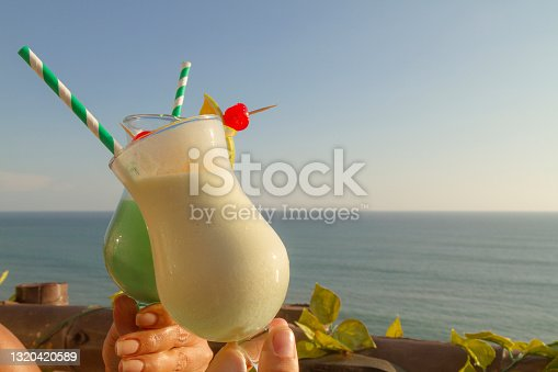 istock A heterosexual couple of Tourists enjoying the landscape at the sunset time, drinking a delicious cocktails in front of the beach. 1320420589