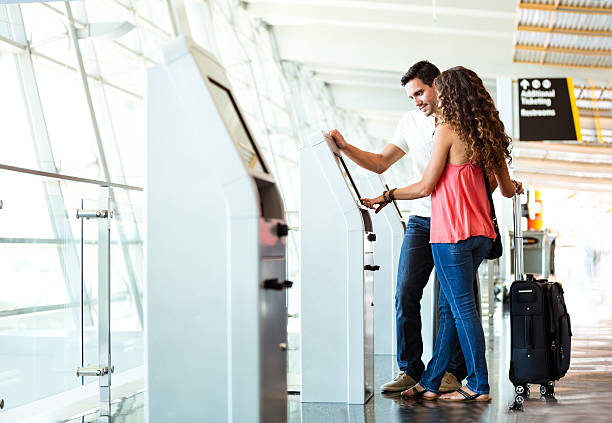 Heterosexual Couple Using Quick Check-In At Airport stock photo