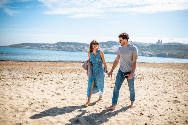 Heterosexual couple walking on the beach and holding hands stock photo