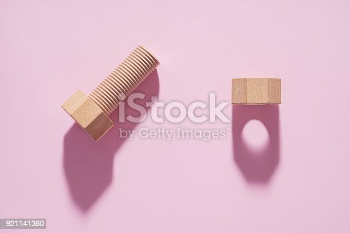 istock Hex nut and bolt on pink background. Build and repair concept, pop art. Wooden bolt and nut. 921141360
