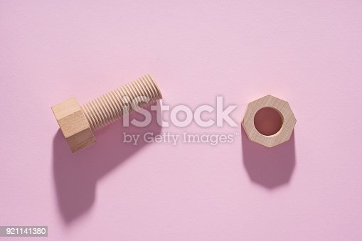 istock Hex nut and bolt on pink background. Build and repair concept, pop art. Wooden bolt and nut. 921141380