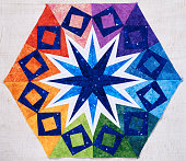Hexagon patchwork block like kaleidoscope from pieces of fabrics, detail of quilt, colors of rainbow