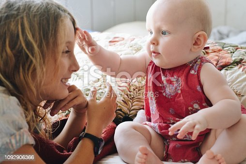 Adorable little baby girl and an older sister or friend sit at home and look at each other. Happy and cute, baby meets big girl