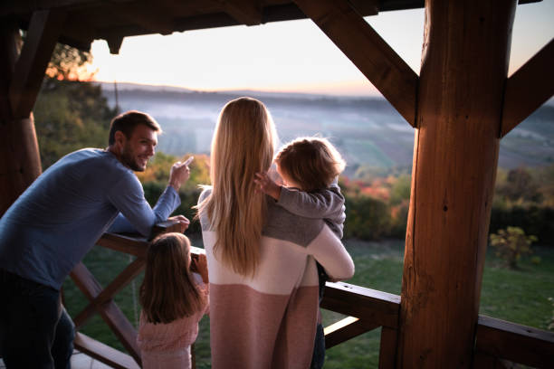 Hey guys, look over there! Family standing together on a balcony while father is pointing at distance. Focus is on mother and son. chalet stock pictures, royalty-free photos & images