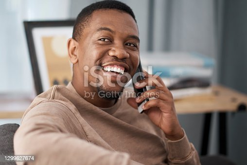 Shot of a young man talking on a cellphone at home