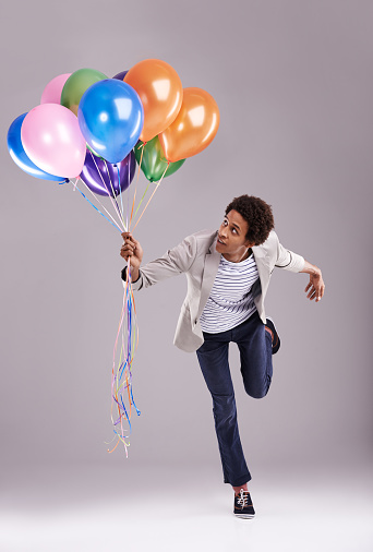 Studio shot of a man being pulled by a bunch of balloonshttp://195.154.178.81/DATA/i_collage/pu/shoots/805348.jpg