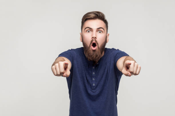Hey you! Amazement bearded man pointing fingers at camera Hey you! Amazement bearded man pointing fingers at camera with open mouth and big eyes. Studio shot anchor athlete stock pictures, royalty-free photos & images