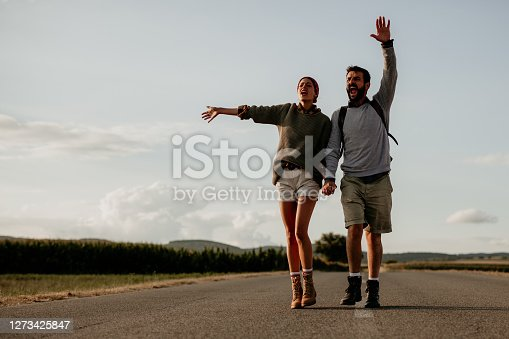 Happy young couple hitchhiking on the road. Traveling and transport concept