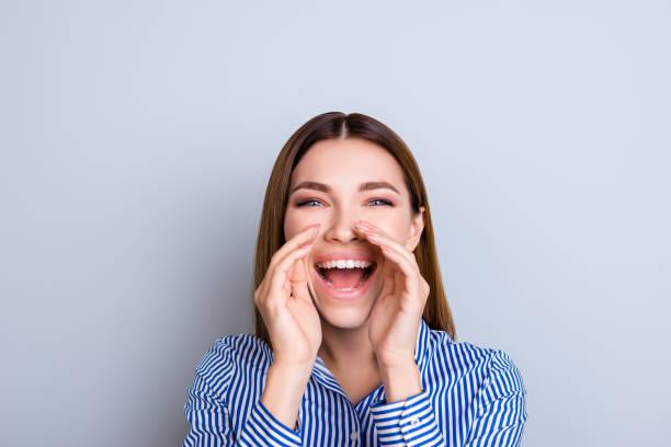 ねえ君!スマート ストライプのシャツで陽気な若い女性が叫び、青の背景に開いた口の近くに手を繋いでいます。 ストックフォト