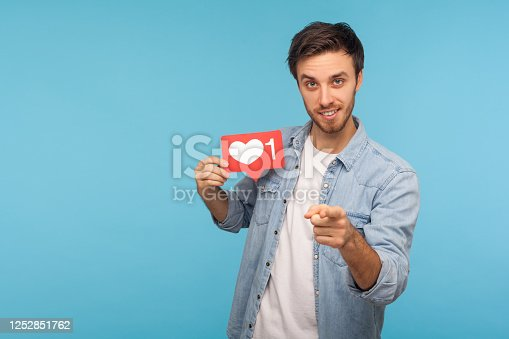 640248524 istock photo Hey you, click Like! Portrait of handsome blogger man in denim shirt holding social media heart Like button 1252851762