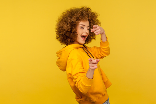 Hey you, handsome! Portrait of joyful curly-haired woman in urban style hoodie winking playfully