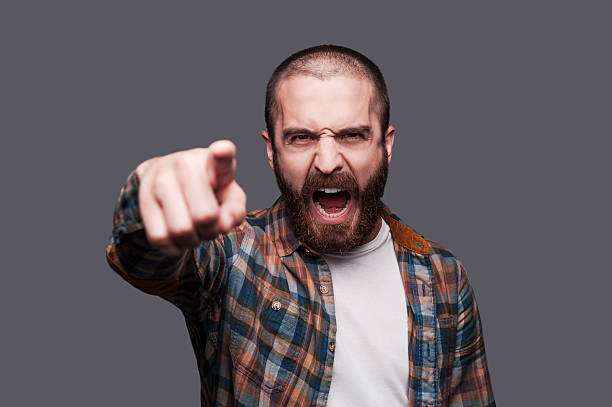 Hey you! Furious young bearded man pointing you and shouting while standing against grey background aggressively stock pictures, royalty-free photos & images