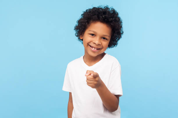 Hey you! Portrait of cheerful funny little boy with curly hair pointing finger to camera and smiling, child making choice indicating at you stock photo