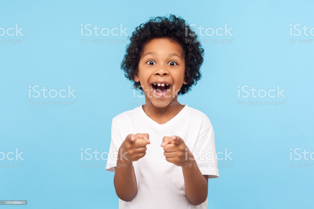 Hey you! Portrait of happy little boy with curly hair pointing finger to camera and laughing loudly with surprised face Hey you! Portrait of happy little boy with curly hair pointing finger to camera and laughing loudly with surprised face, teasing making fun of you. indoor studio shot isolated on blue background African Ethnicity Stock Photo