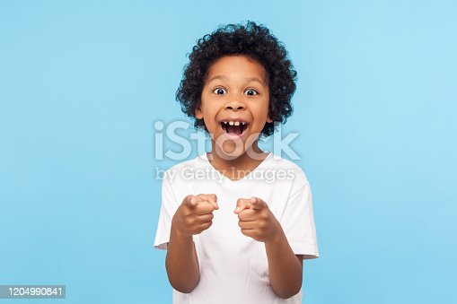 Hey you! Portrait of happy little boy with curly hair pointing finger to camera and laughing loudly with surprised face, teasing making fun of you. indoor studio shot isolated on blue background