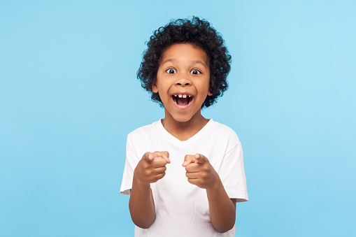 Hey You Portrait Of Happy Little Boy With Curly Hair Pointing Finger To Camera And Laughing Loudly With Surprised Face Stock Photo - Download Image Now