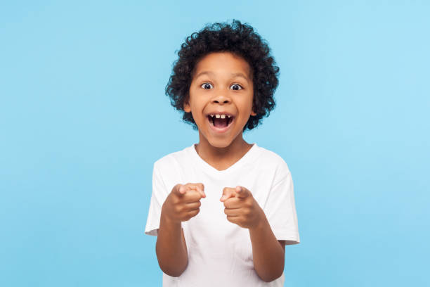 Hey you! Portrait of happy little boy with curly hair pointing finger to camera and laughing loudly with surprised face Hey you! Portrait of happy little boy with curly hair pointing finger to camera and laughing loudly with surprised face, teasing making fun of you. indoor studio shot isolated on blue background excited stock pictures, royalty-free photos & images