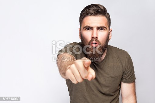 istock Hey You! Portrait of surprised excited bearded man with dark green t shirt against light gray background 826740932