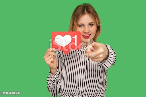 640248524 istock photo Hey you, put like to content! Pretty girl with red lips in glamour striped blouse holding social media heart icon 1206416320