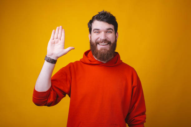 Hi friends, smiling man with beard in red blouse making Hello gesture Hi friends, smiling man with beard in red blouse making Hello gesture red shirt stock pictures, royalty-free photos & images