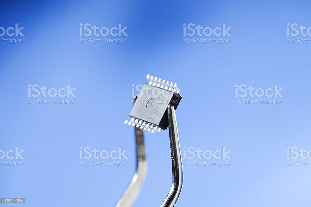 Hi Tech Electronics - Tweezers Holding Microchip stock photo