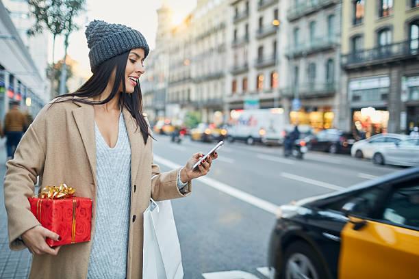 hialing a taxi with smart phone app. christmas shopping. - weihnachtsprogramm stock-fotos und bilder
