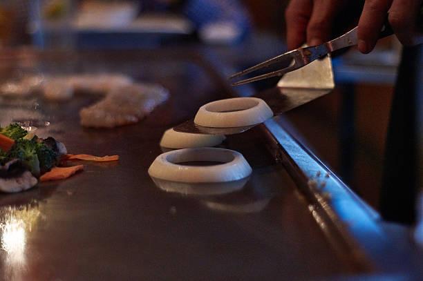 hibachi chef stack onion rings with spatula stock photo