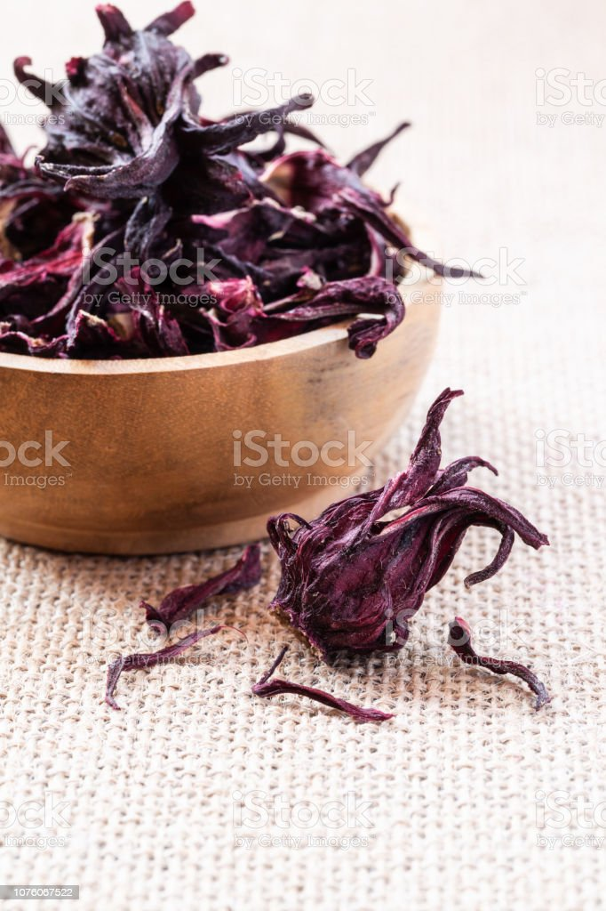 Hibiscus dry flowers in wooden bowl on burlap background with...