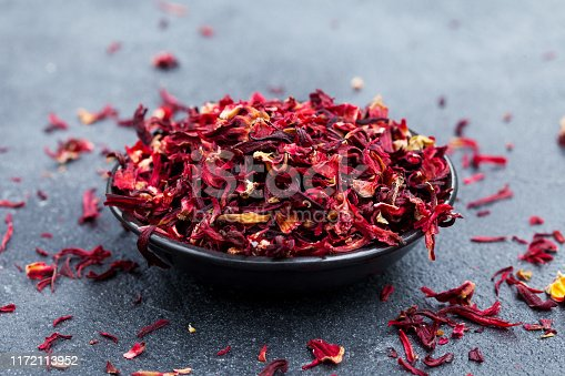 Hibiscus tea in black bowl. Slate background. Close up.