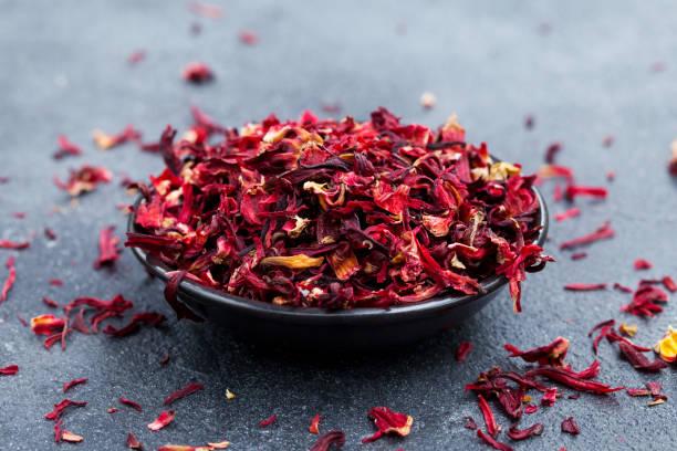 hibiscus te i svart skål. skiffer bakgrund. närbild. - foderblad bildbanksfoton och bilder