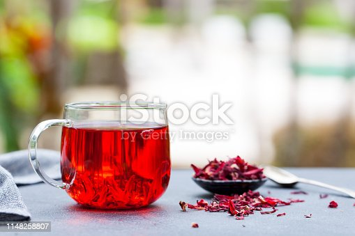 Hibiscus tea in glass cup. Grey background. Copy space. Outdoor background
