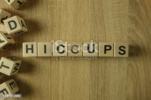 Hiccups word from wooden blocks on desk