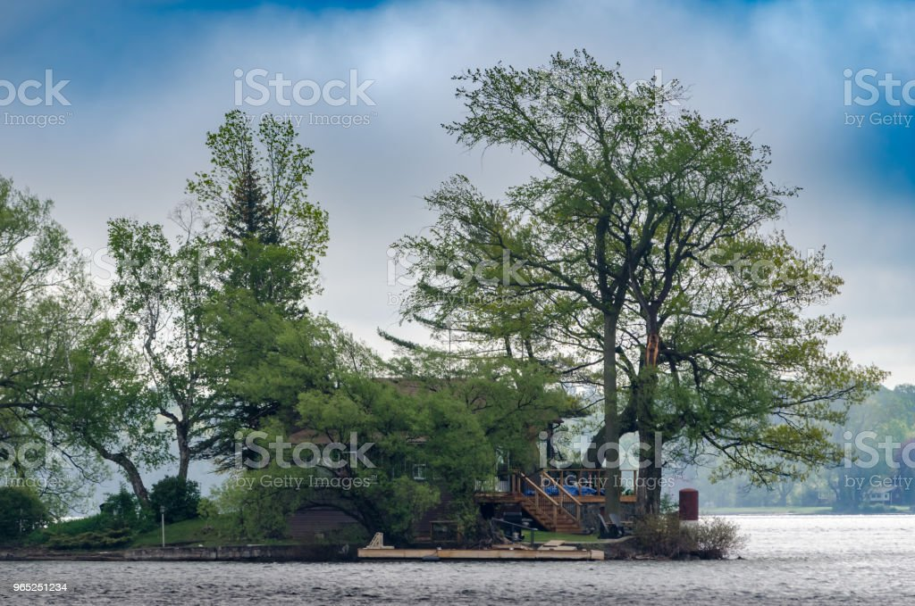 Hidden cottage on an island point in the St. Lawrence River with foggy shoreline in the background. zbiór zdjęć royalty-free