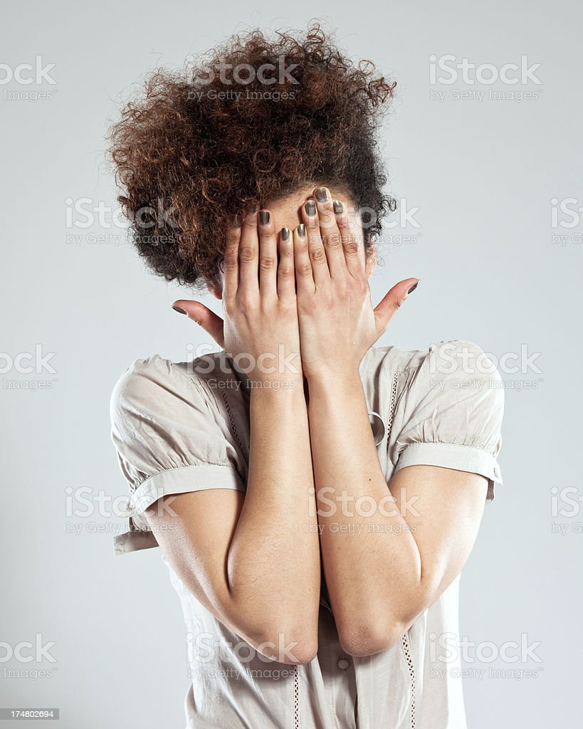 Hidden Girl Portrait of afro girl covering her face with hands. Studio shot, grey background. 18-19 Years Stock Photo