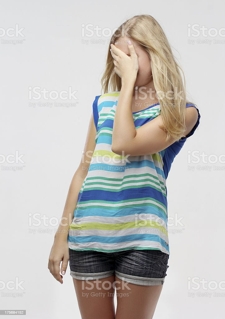 Hidden girl.Young woman covering her eyes with hands royalty-free stock photo