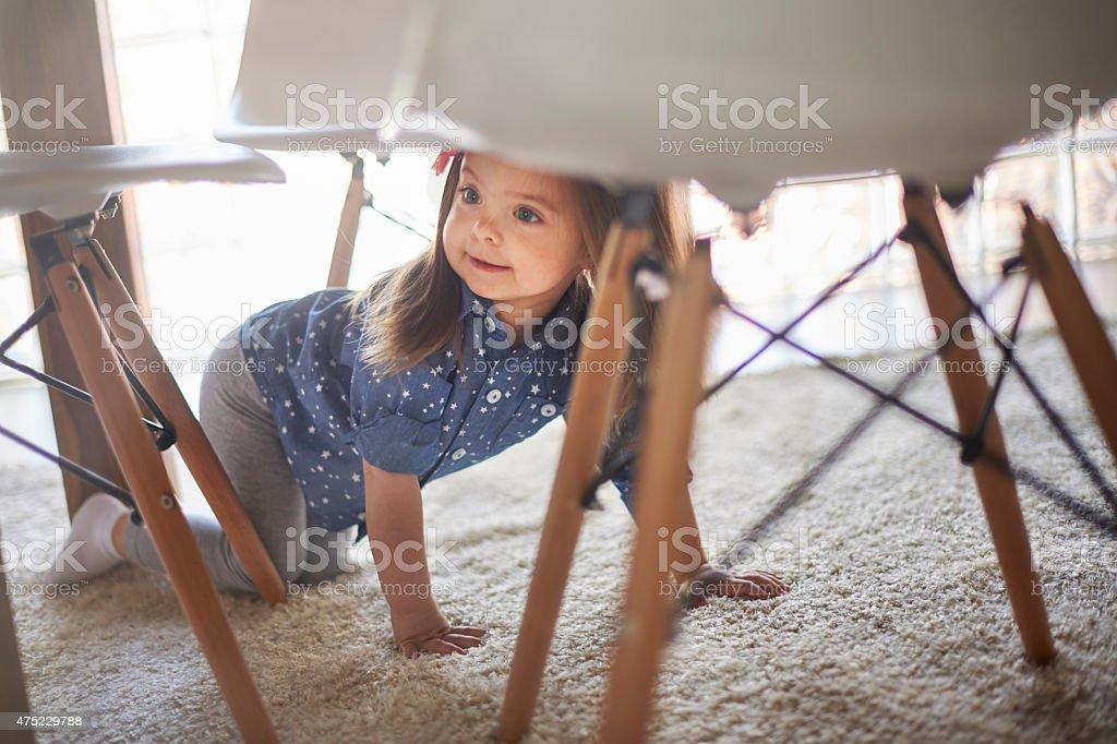 Hidden little girl under the table stock photo