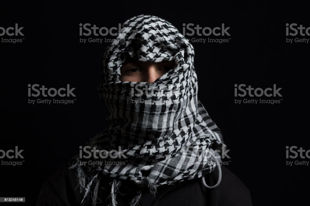 hidden man with palestinian scarf over head in front of isolated black background stock photo