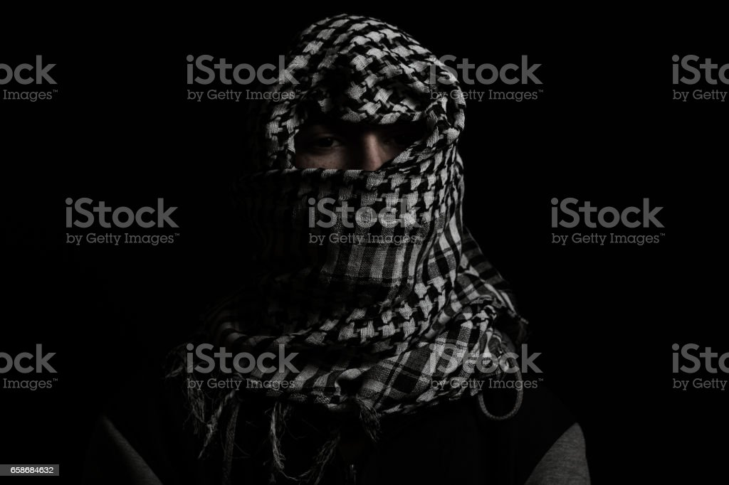 hidden man with palestinian scarf over head stock photo