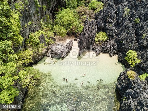 Beautiful hidden beach on majestic Matinloc Island, hidden small tropical lagoon and beach surrounded with rock formations. Aerial Drone Point of View. Matinloc Island, Mimaropa, El Nido, Palawan, Philippines, Asia